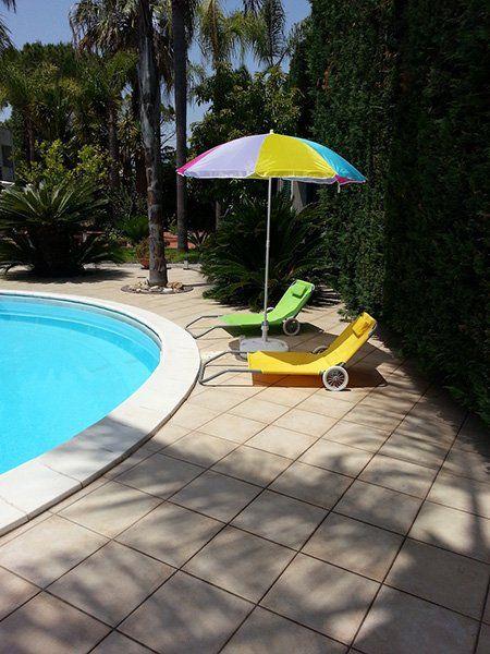 vista angolare da bordo piscina sdraio gialli e verdi e ombrellone multicolore