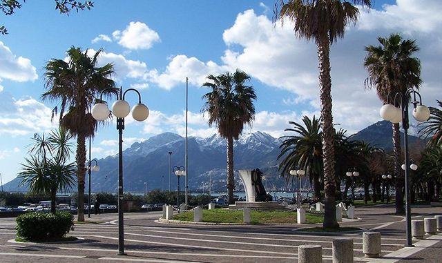 Vista del  lago, delle montagne e cielo chiaro. Piazza con palme e lampioni