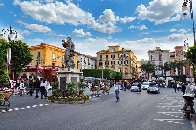 Vista del piazzale, una statua al centro con fiori gialli intorno. Macchine sulla strada, persone che camminano sul marciapiedi