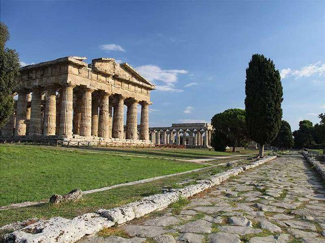 ingresso a un giardino con dei monumenti stile Partenone con dei pini