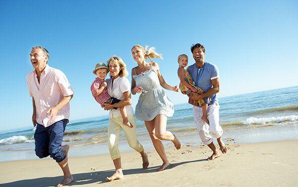 delle coppie sorridenti con dei bambini in braccio in una spiaggia