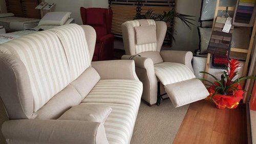 esposizione di poltrona e divano a righe bianche e grigie