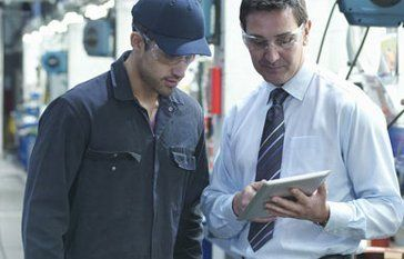 2 workers looking at a tablet