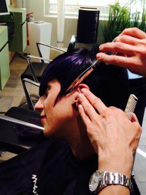 una parrucchiera che taglia i capelli di una ragazza