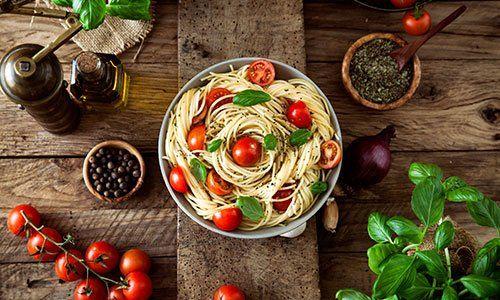 Cucina italiana. Pasta con olio d'oliva, aglio, basilico e pomodoro e zuppa di pomodoro.