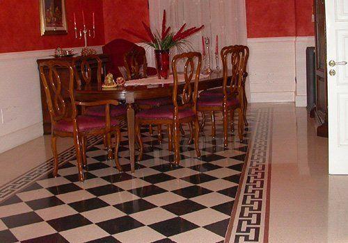 una sala da pranzo con un tavolo e un pavimento a scacchi di color bianco e nero