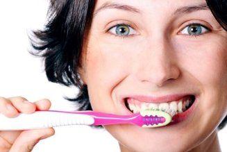 una donna mentre lava i denti con uno spazzolino
