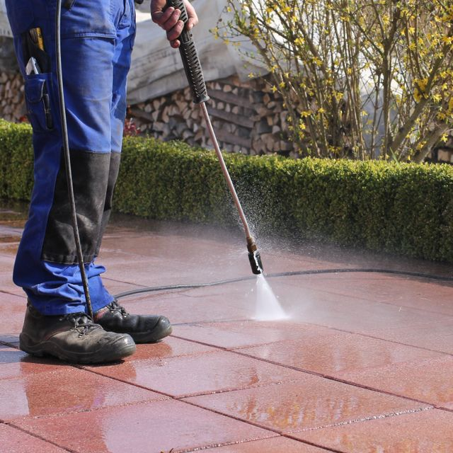 A cleaner from Roth Pressure Cleaning Services cleaning red tiles
