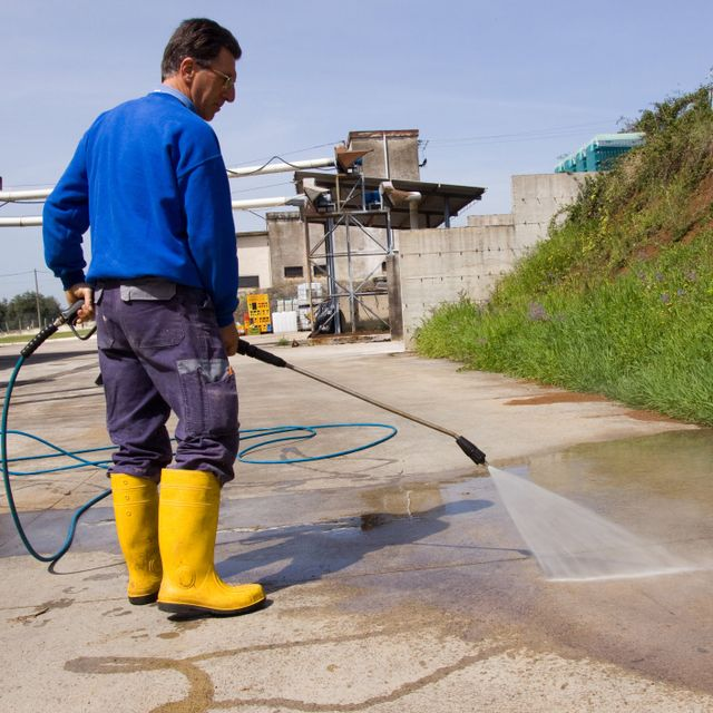 A cleaner from Roth Pressure Cleaning Services cleaning the pavement