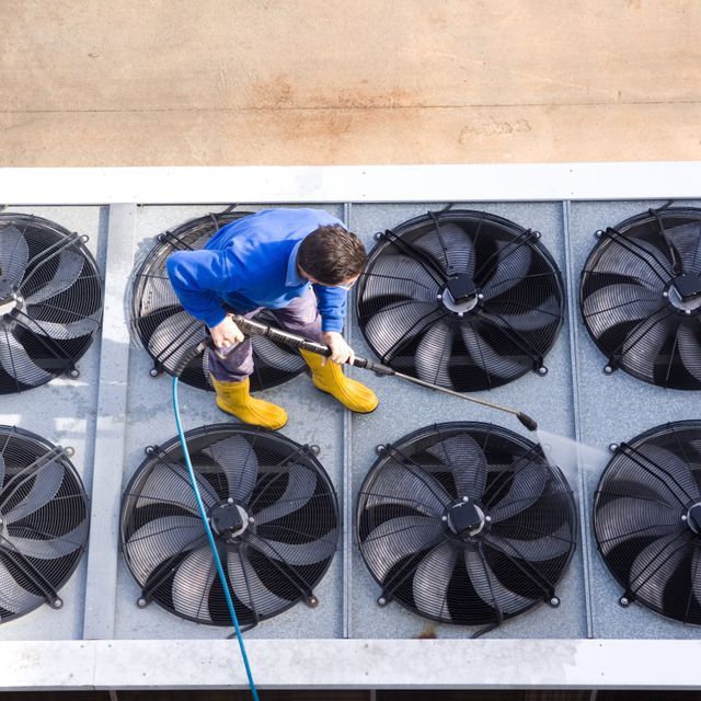 A cleaner from Roth Pressure Cleaning Services cleaning large metal fans on top of a building