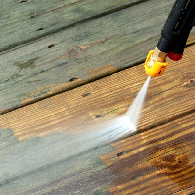 Closeup of a pressure cleaner cleaning a wooden deck