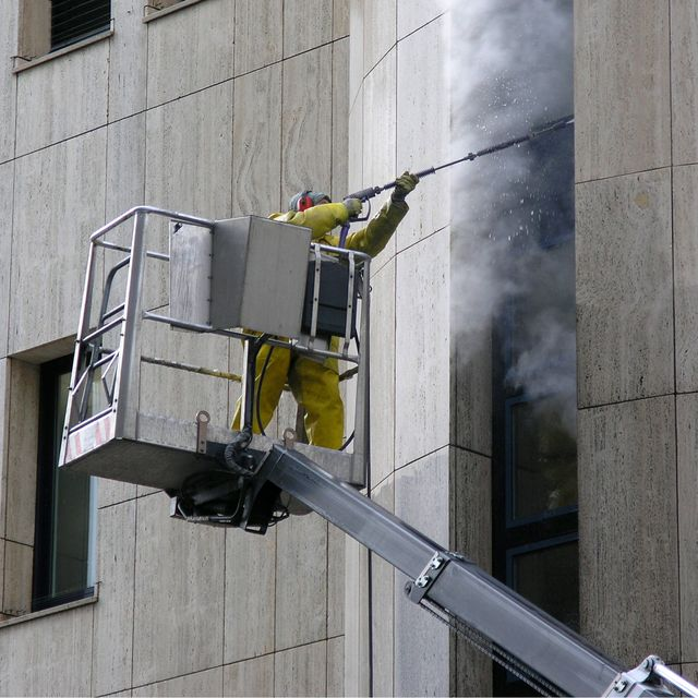 A cleaner from Roth Pressure Cleaning Services cleaning the side of a building from a crane