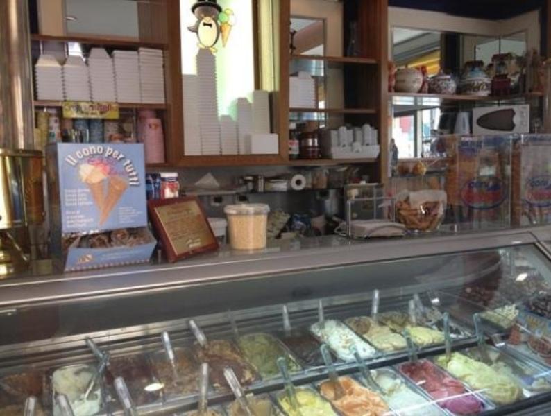 Interno del negozio che mostra il banco frigo con le vaschette di gelato di vari gusti