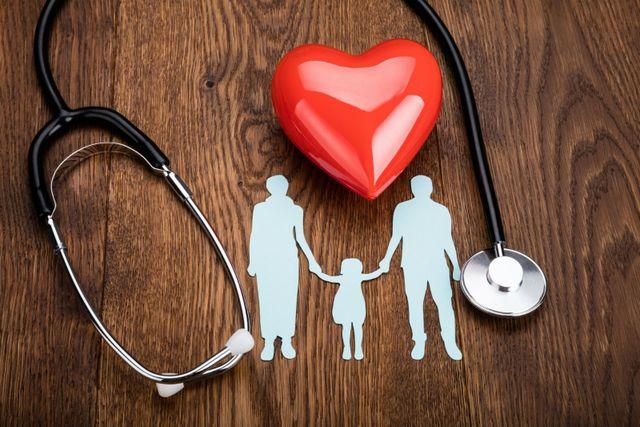 uno stetoscopio con un cuore di plastica e il disgno di una famiglia