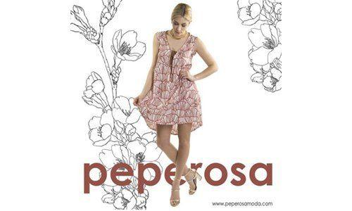una donna con un vestito bianco a disegni rosa e la scritta Peperosa