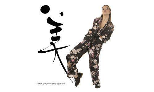 una donna con un kimono nero a fiori e un ideogramma giapponese