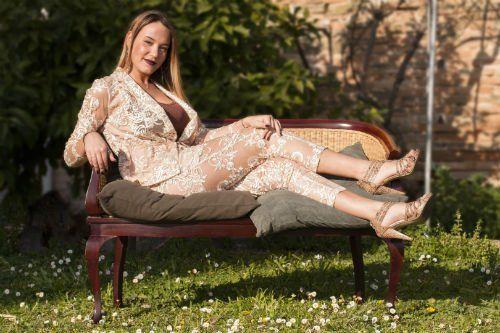 Una donna seduta su un divano in un giardino