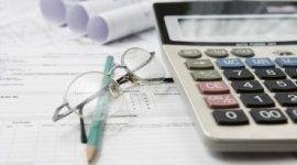 calcolatrice con occhiali da vista e matita sopra un documento