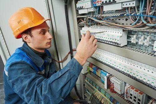un elettricista con in mano un cacciavite, fissa dei bulloni in una centralina elettrica