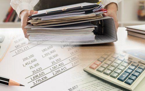 impiegata prende in mano dei raccoglitori contabili