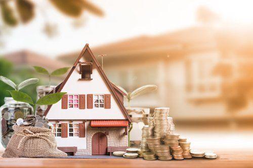 modellino di casa con pila di monete