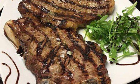 una bistecca grigliata in un piatto con foglie di insalata e decorazioni di aceto balsamico