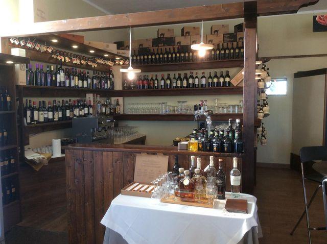 un tavolino con una tovaglia bianca e sopra delle bottiglie, dietro un bancone in legno con sopra altre bottiglie e in fondo delle mensole in legno con dei vini  e sotto dei bicchieri