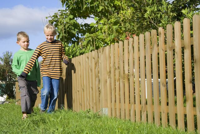 boys playing by wooden fence