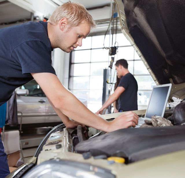 Mechanics at computer analyzing clutch parts in Anchorage, AK
