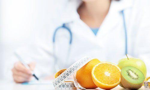 La dottoressa nutricionista scrivendo e sulla tavola un metro e più frutta