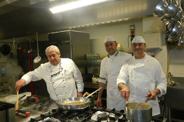 tre cuochi in cucina mentre cucinano