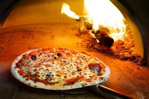 una pizza vicino al forno a legna