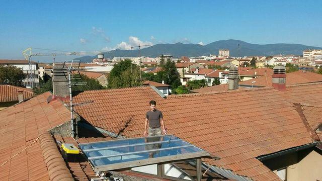 un uomo su un tetto di fronte una copertura in vetro