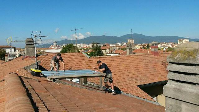 due uomini che installano una copertura di vetro su un tetto