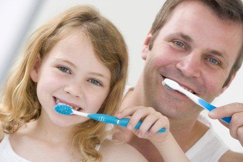 Father and daughter brushing teeth in Moody, AL