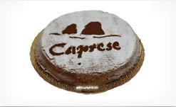 una torta con zucchero a velo e la scritta Caprese