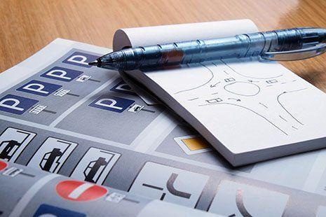 un libro da scuola guida , una penna e un blocchetto con un disegno di un incrocio