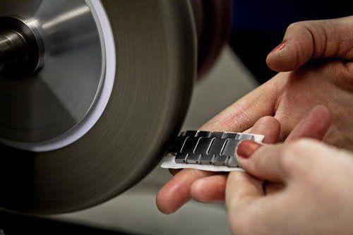 due mani con un cinturino in acciaio e un disco levigatore
