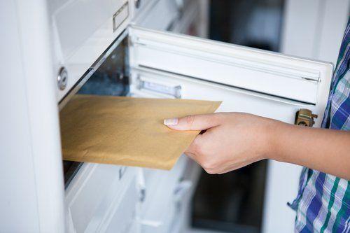 persona prende una busta dalla buchetta della posta