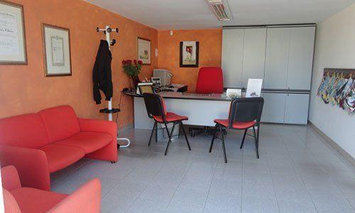 un ufficio con divano,poltrona e sedie rossa, una scrivania, un armadio bianco e pareti color arancione