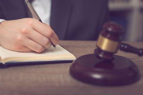 avvocato mentre scrive su un foglio in studio legale