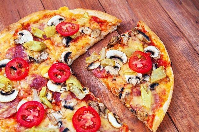 una pizza con funghi e pomodori freschi
