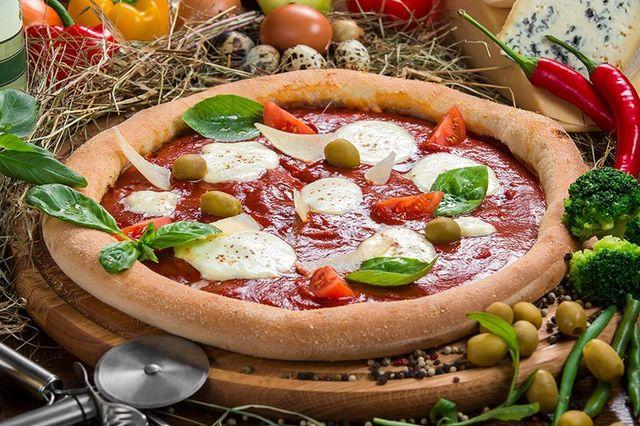 una pizza con pomodoro,mozzarella fresca, olive e basilico