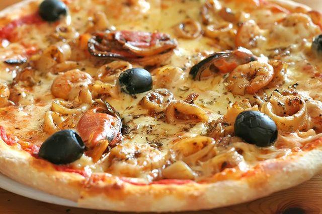 una pizza ai frutti di mare e olive nere