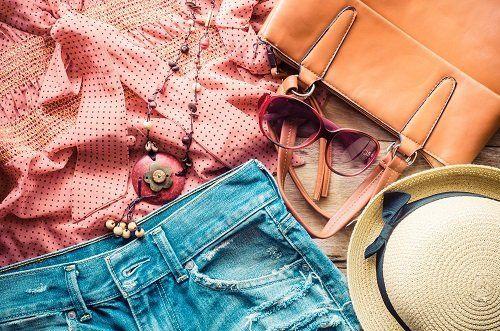 vestiti e accessori (cappello, collane e occhiali) messi su un tavolo