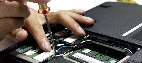 Man inrepairing a laptop using screw driver