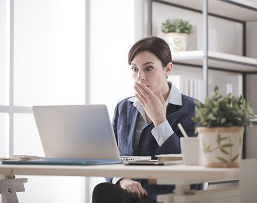 Young businesswoman having problems with her computer, she is staring shocked at the screen with an hand over mouth