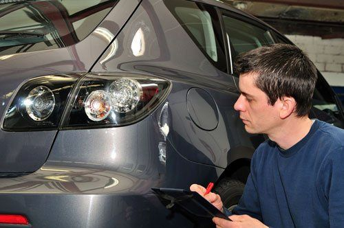 An insurance agent inspecting a car