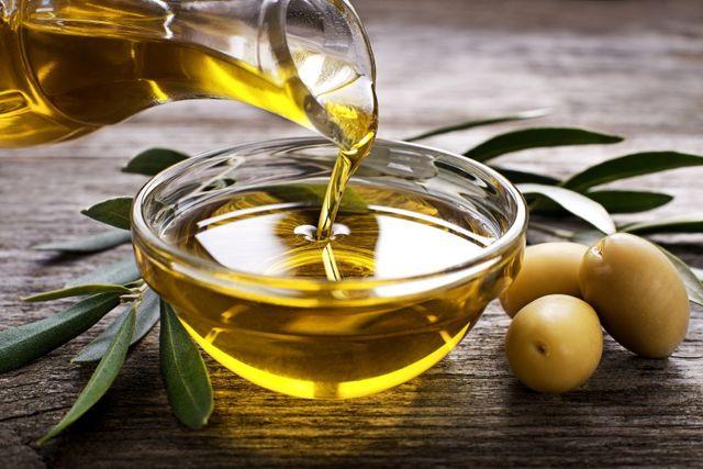olio versato in una ciotola con vicino foglie di ulivo e olive