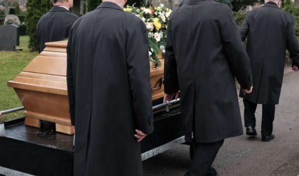Uomini vestiti di nero portando la bara